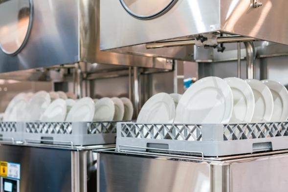 Gewerbliche Spülmaschine mit aufgereihten Tellern