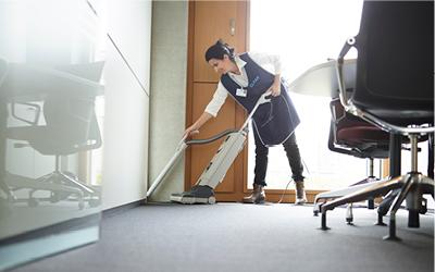 Dame saugt den Boden im Hotelzimmer mit Staubsauger