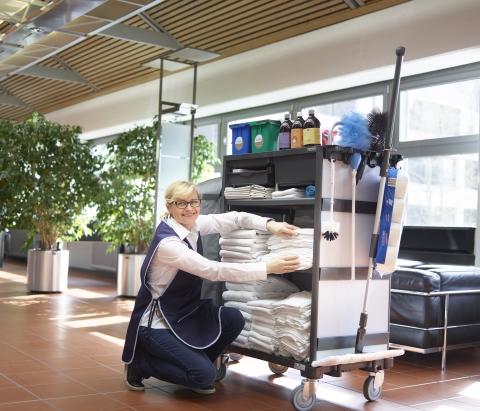 Hotelreinigung in Köln Bonn Mitarbeiterin lächelt freundlich mit Handtuch in der Hand