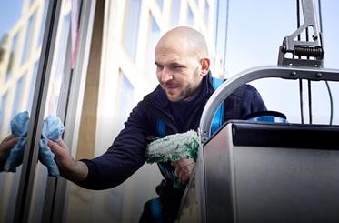 Lächelnder Mitarbeiter Gebäudereinigung und Fensterreinigung im Einsatz von Clean.de