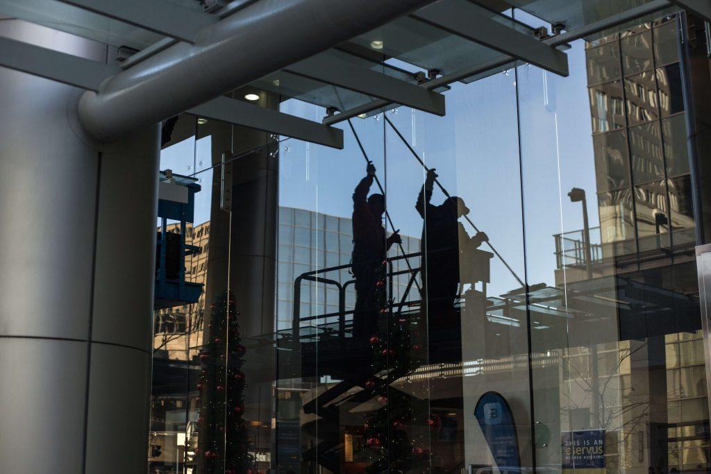 Gebaeudereiniger bei der Arbeit am Fenster